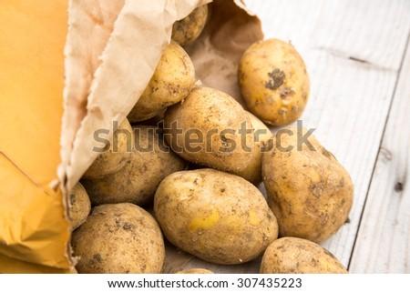 Bag of rustic dirty white potatoes - stock photo