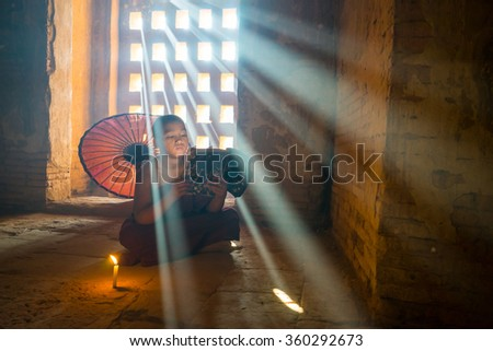 BAGAN, MYANMAR - DEC 11, 2015: Unidentified Buddhism neophyte read a book in Buddihist temple on December 11, 2015 in Bagan, Myanmar. Southeast Asian neophyte reading a book in a Buddihist temple - stock photo