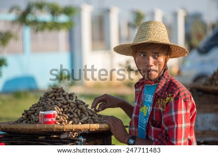 BAGAN, MYANMAR - FEBRUARY 6: Burmese man sells peanuts on February 6, 2014 in Bagan. Myanmar is ethnically diverse with 51 million inhabitants belonging to 135 ethnic groups. - stock photo