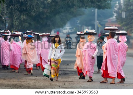 BAGAN, MYANMAR, JANUARY 25, 2015 : A row of Buddhist nuns carrying plates on head for morning alms is walking in the streets of Bagan in Myanmar (Burma) - stock photo