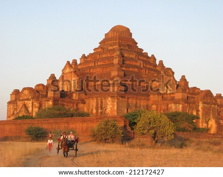 BAGAN, MYANMAR: JANUARY 1, 2010:  Tourists take a carriage ride at dusk at Bagan's largest Buddhist temple, Dhammayangyi. - stock photo