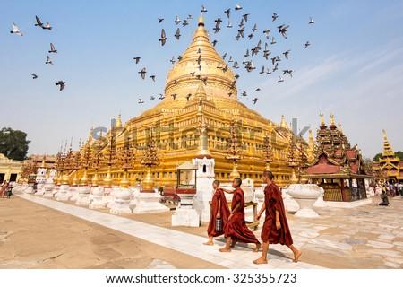 Bagan, Myanmar - March 15: Novice Buddhist monks walking around the sacred Shwezigon Paya, one of Myanmar's most revered pagodas, in Nyaung U, Bagan, Myanmar (Burma). - stock photo