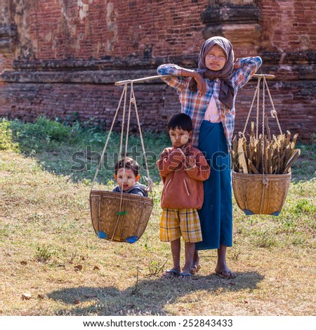 BAGAN, MYANMAR - NOVEMBER 26, 2014: an unidentified Burmese woman walks in the fields among the ancient temples with her two sons and the firewood on his shoulders - stock photo