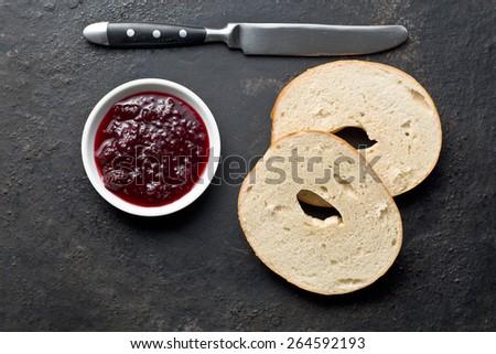 bagel and jam on black background - stock photo