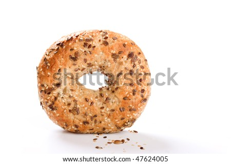 Bagel stood on edge with seeds in foreground - stock photo
