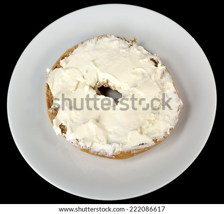 Bagel with cream cheese on a plate on a black background. - stock photo