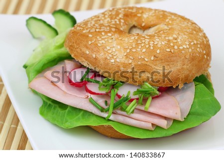 Bagel with ham, lettuce, cucumber and radish, close up  - stock photo