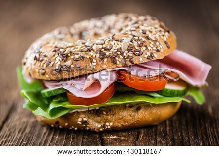 Bagel with Ham (selective focus) on an old woden table (close-up shot) - stock photo
