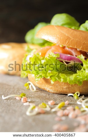 bagel with salmon and germinated sprouts pink salt on a stone background - stock photo