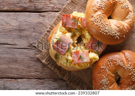bagel with scrambled eggs and bacon close-up on the table. horizontal view from above  - stock photo