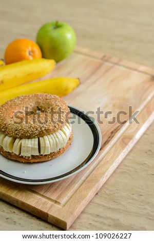 Bagel with sliced banana - stock photo