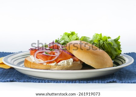 Bagel with Smoked Salmon Lox, cream cheese and red onion accompanied by lettuce salad. - stock photo