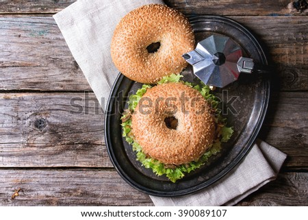 Bagel with stew beef, fresh salad and fried onion served on vintage metal tray with coffee pot over wooden table. Top view - stock photo