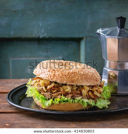 Bagel with stew beef, fresh salad and fried onion served on vintage metal tray with coffee pot over wooden table. Square image - stock photo