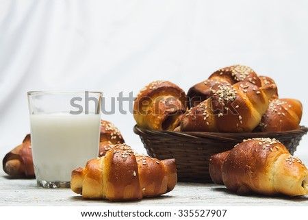 bagels with a glass of milk on a blurred background basket with bread rolls on white wooden background - stock photo