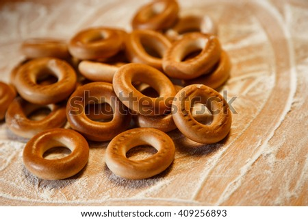 Bagels with flour on wooden background. Selective focus. - stock photo