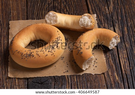 Bagels with poppy seeds on old wooden table - stock photo