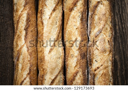 Baguette bread loaves in a row on wooden background - stock photo