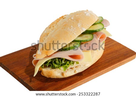 Baguette roll with ham, cheese, lettuce and cucumber slices on a wooden board - stock photo