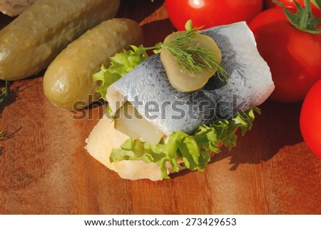 Baguette slice with sour herring, pickled herring, garnished with lettuce, gerkin, dill, tomatoes and onion on a wooden chopping board - stock photo