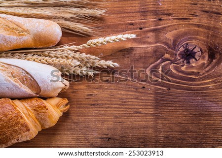 baguettes and croissant with wheat ears on old wooden board  - stock photo