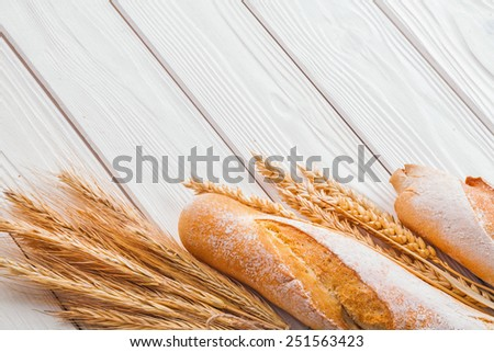 baguettes and ears of wheat on old white wooden boards with copyspace  - stock photo