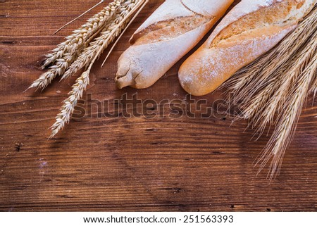 baguettes and ears of wheat on old wooden boards  - stock photo