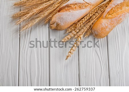 baguettes and ears of wheat rye on vintage wooden painted boards food and drink concept  - stock photo