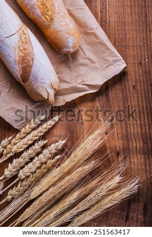 baguettes on paper  and ears of wheat  old wooden board  - stock photo
