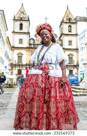 BAHIA, BRAZIL - CIRCA NOV 2014: A Brazilian woman of African descent, smiling, wearing traditional clothes from the state of Bahia in the old colonial district of Salvador (Pelourinho). - stock photo