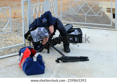 BAIKONUR, KAZAKHSTAN -?? NOVEMBER 23, 2014: Unidentified European Space Agency photographer installs a remote camera before the launch of Soyuz TMA-15M spacecraft 100 m away from the launch vehicle - stock photo