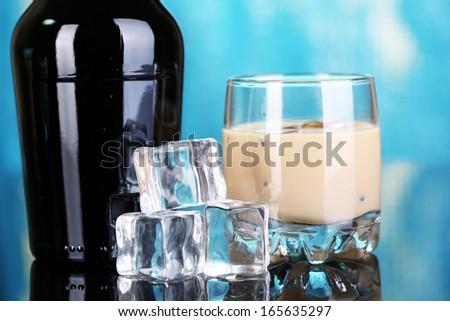 Baileys liqueur in bottle and glass on blue background - stock photo