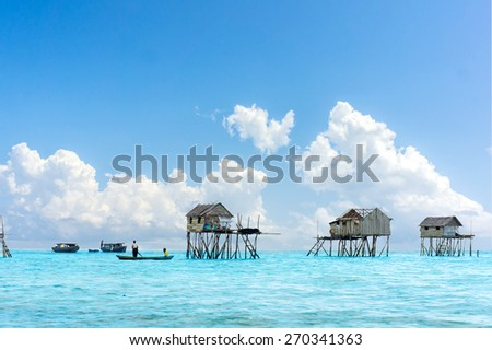 bajau floating village and blue sky - stock photo