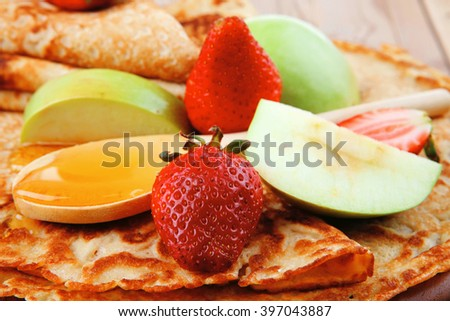 baked and fruits : pancake with honey strawberries and apple on wooden table - stock photo