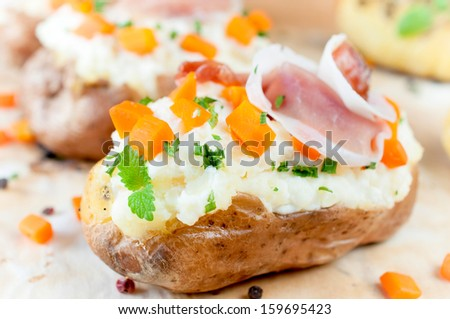 Baked and stuffed potato on the table  - stock photo