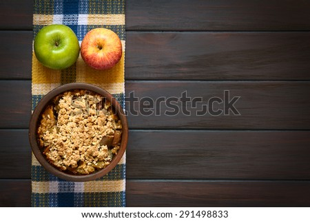 Baked apple crumble or crisp in rustic bowl with fresh apples on a kitchen towel, photographed overhead on dark wood with natural light - stock photo