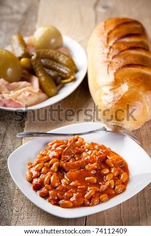 Baked beans and bacon with pickles and bread - stock photo