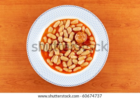 Baked beans and chorizo in tomato sauce on wood background. Shallow depth of field - stock photo