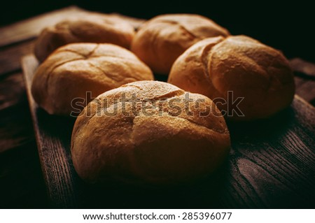 Baked bread servings on wooden board made using ancient bakery methods - stock photo