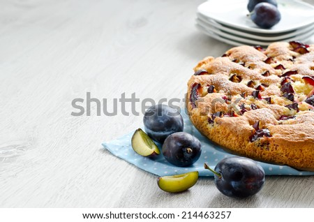 Baked cake with plums, copy space wooden background - stock photo