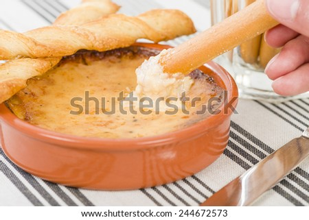 Baked Cheese - Melted cheese dip served with breadsticks. - stock photo