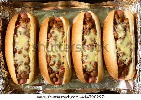 Baked cheesy chili hot dogs in baking pan, photographed overhead with natural light - stock photo