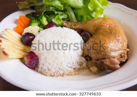 Baked chicken and rice on white plate, decorated with vegetables, salad and fruit. - stock photo