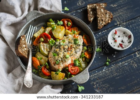Baked chicken breast with vegetables in a vintage pan on a  dark wood surface. Healthy food, rustic style - stock photo