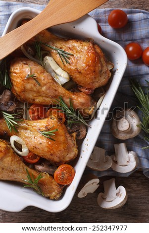 Baked Chicken drumsticks with vegetables and mushrooms close up. vertical top view  - stock photo