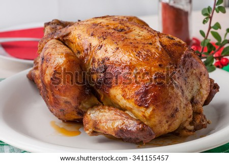 Baked chicken for Christmas dinner on white plate. - stock photo