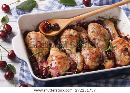 Baked chicken leg with cherry and rosemary in dish for baking close up. Horizontal