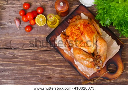 baked chicken with a golden crust with vegetables on a wooden background - stock photo