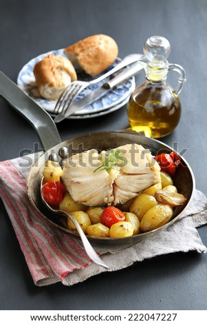 Baked cod fish with potatoes and vegetables - stock photo