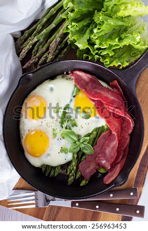 Baked eggs with asparagus and turkey bacon - stock photo